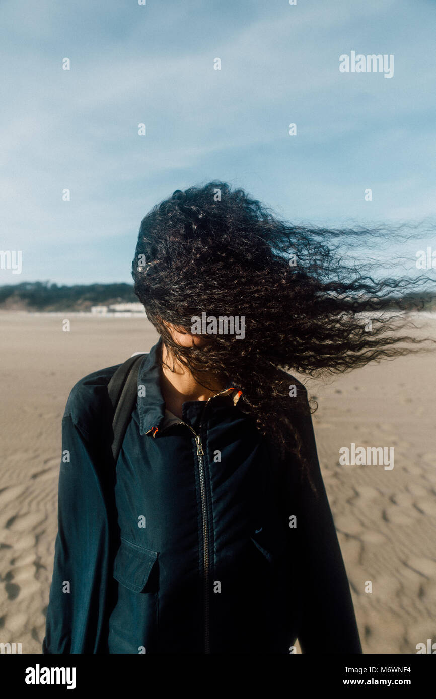 Woman on the Beach with Hair in Her Face - Stock Image
