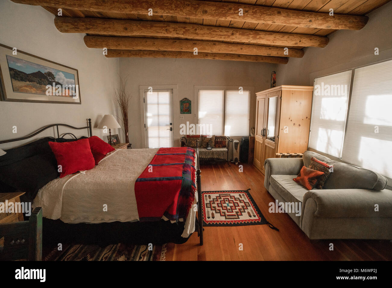 A Quaint Santa Fe, New Mexico Bedroom In An Adobe Architecture Style Home  With Wooden Floors, Log Ceiling, And White Walls.