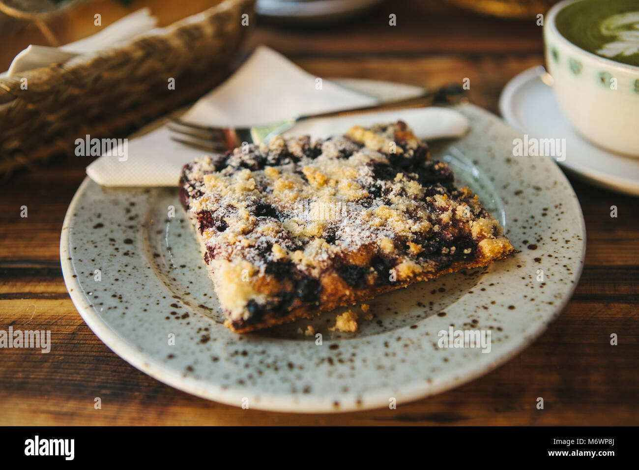 Close-up piece of sweet pie with dessert fork on saucer against background of blurry plates with food on wooden - Stock Image