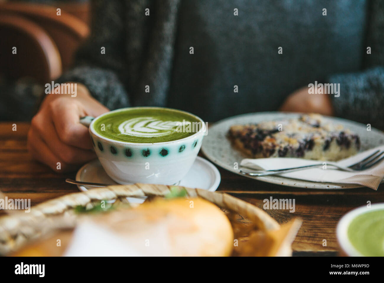 The girl sitting in cafe and holding mug with green tea with milk next to piece of sweet pie and two sandwiches - Stock Image