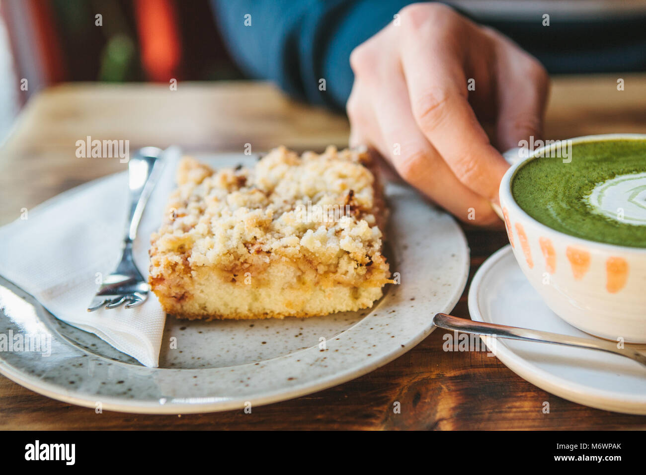 Close-up man's hand holding mug of green tea with beautiful pattern in the form of white foam next to dessert - Stock Image