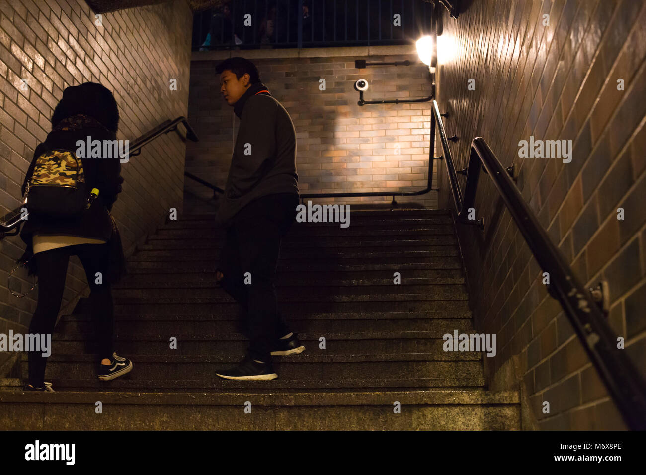 A man and a woman in a brick stairwell at night with some tension between them. - Stock Image