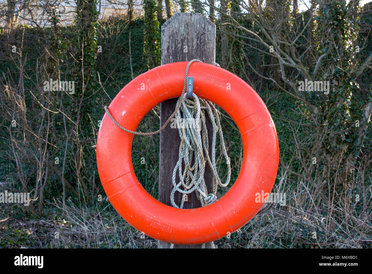 an orange rubber or plastic lifebuoy or perrybouy on a stand at the seaside for thtowing into water to save lives Stock Photo
