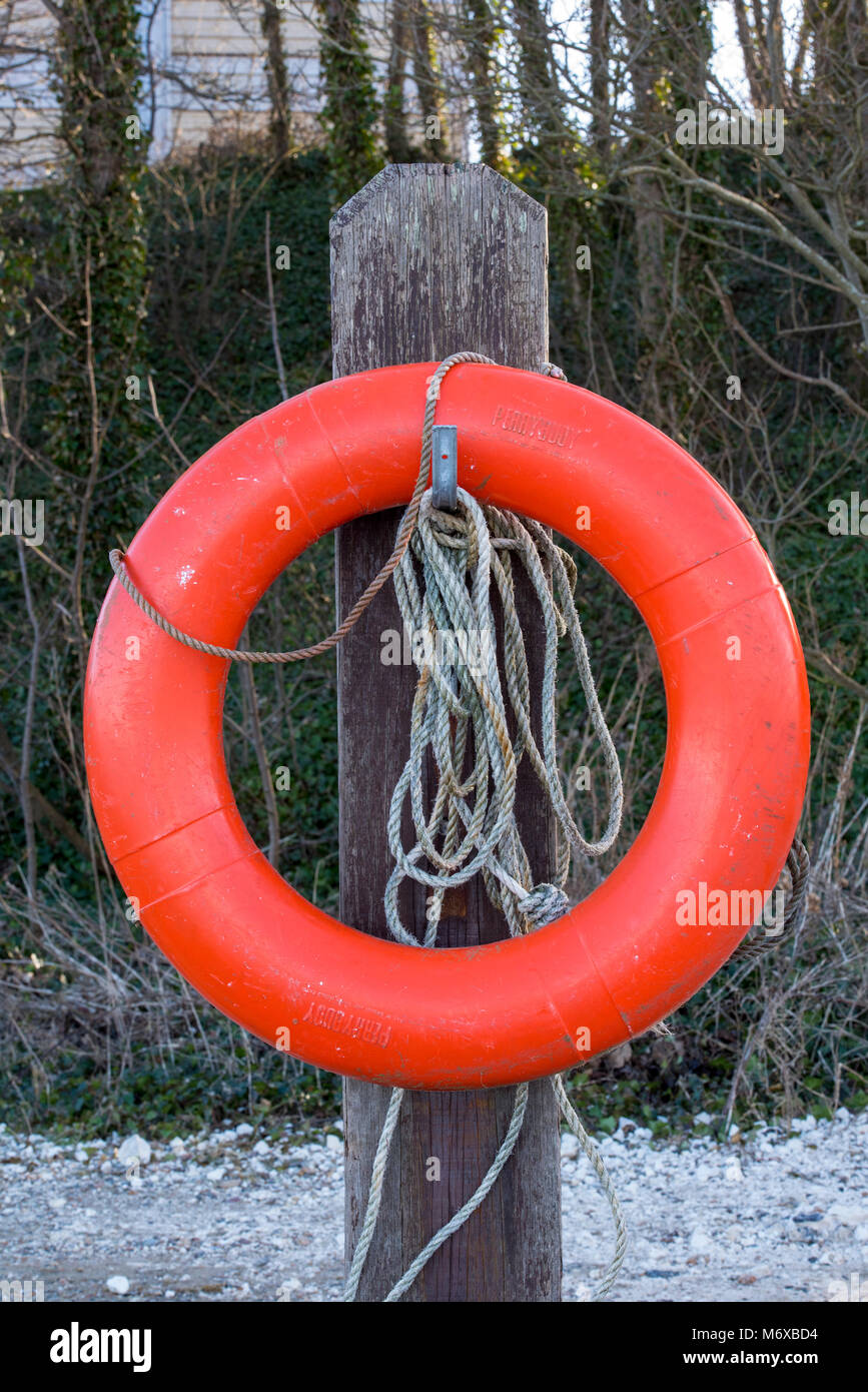 An orange perry buoy or life buoy rubber ring or floatation device for lifesaving near water on a wooden post with Stock Photo
