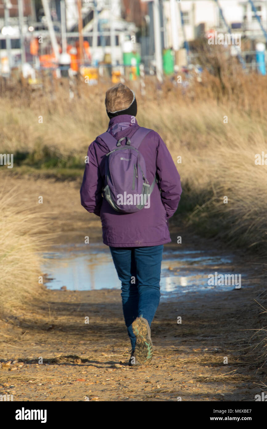 an older or middle aged woman or lady walking along a country lane approaching a puddle on the pathway or track. - Stock Image