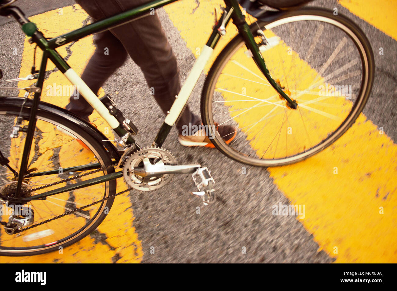 man walking his bike in a park - Stock Image
