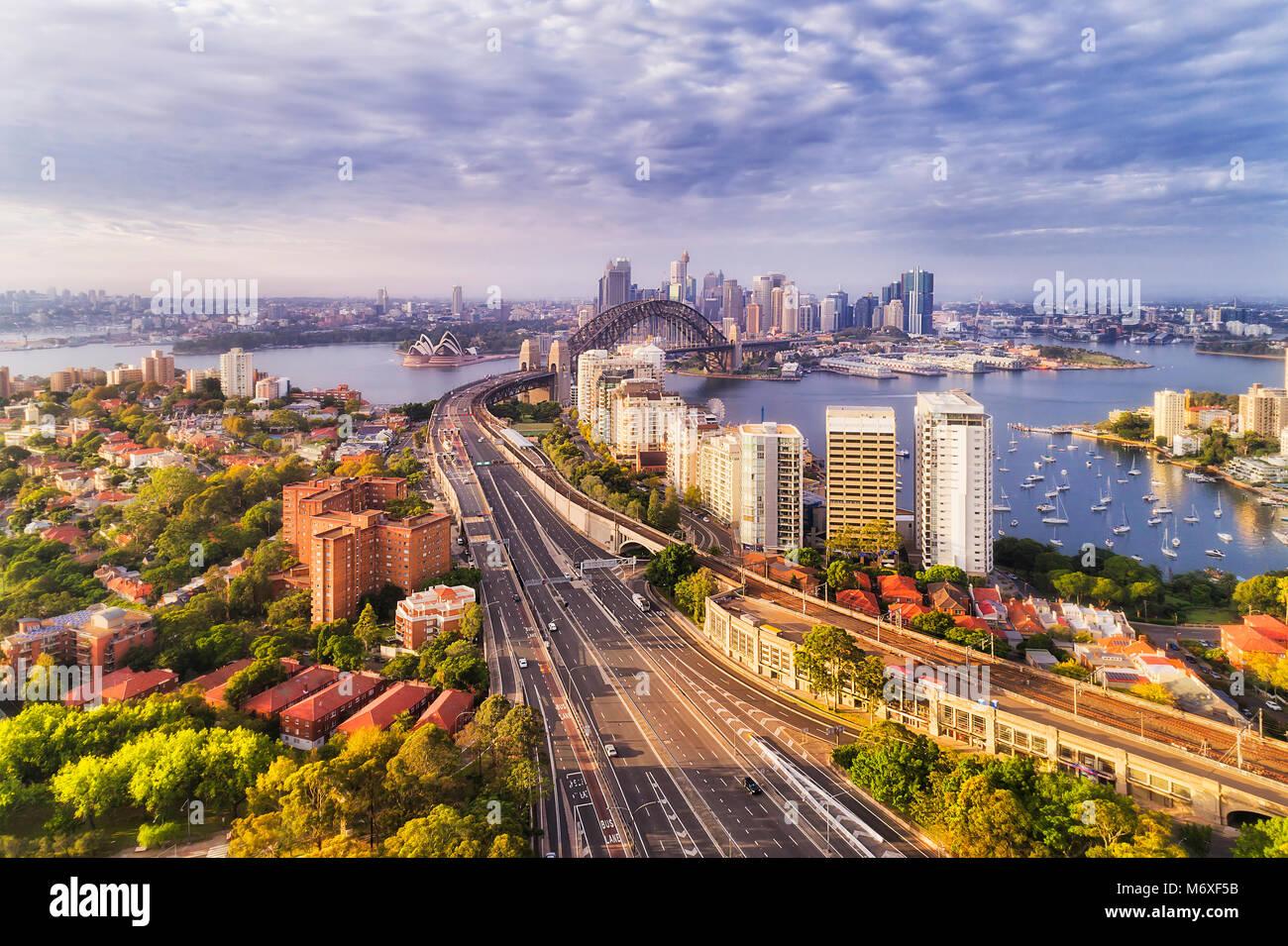 Soft morning light over Sydney city landmarks on both sides of harbour - from North Sydney Warringah freeway via - Stock Image