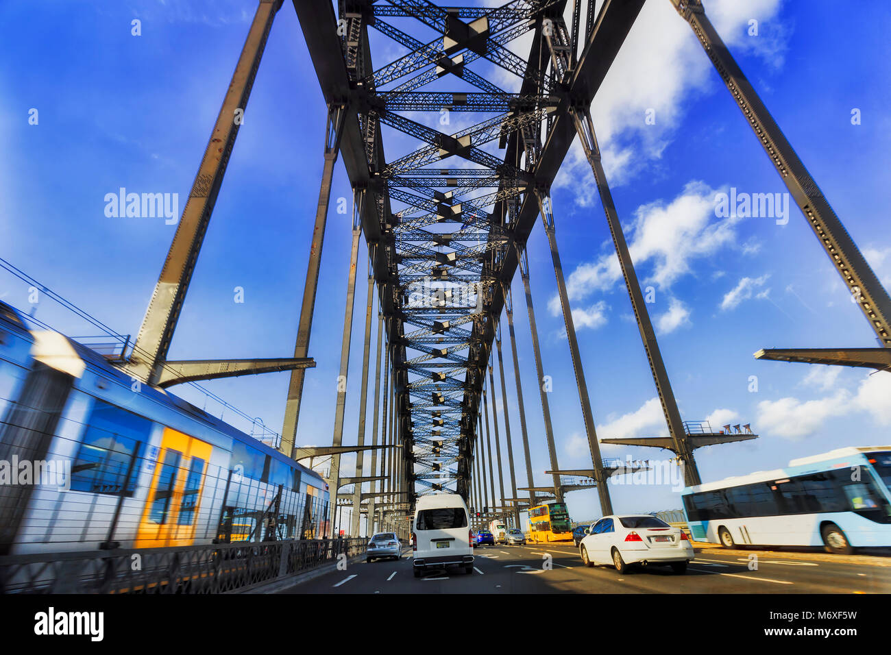 Public transportation and private passenger cars during intense traffic rush hour driving over Sydney harbour bridge - Stock Image