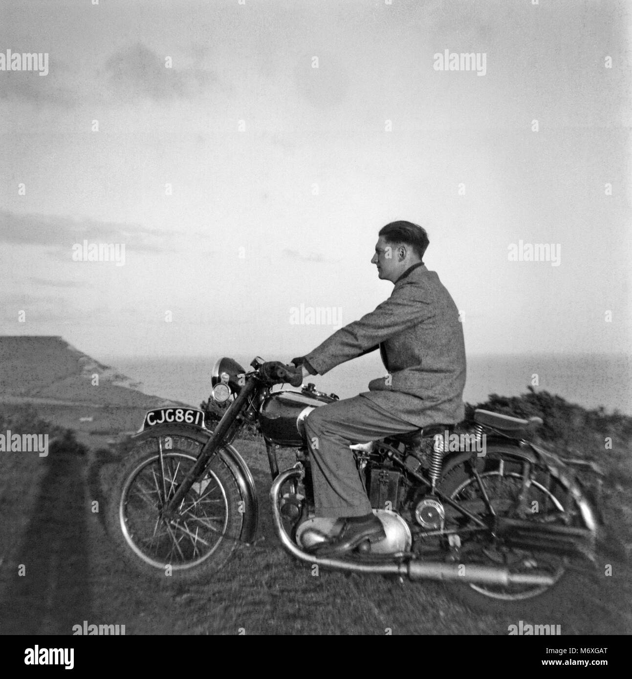 Vintage photo of a man riding a Triumph Motorcycle in England during the 1930s. - Stock Image