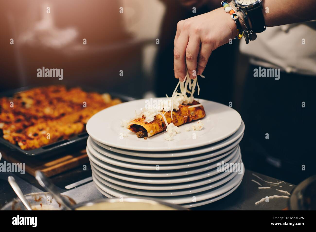 Woman preparing delicious mexican enchiladas. Culinary workshops Stock Photo