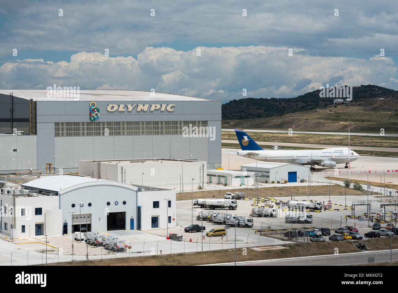 Olympic Airways hangar and logo with fuel trucks in foreground on Athens International Airport Stock Photo