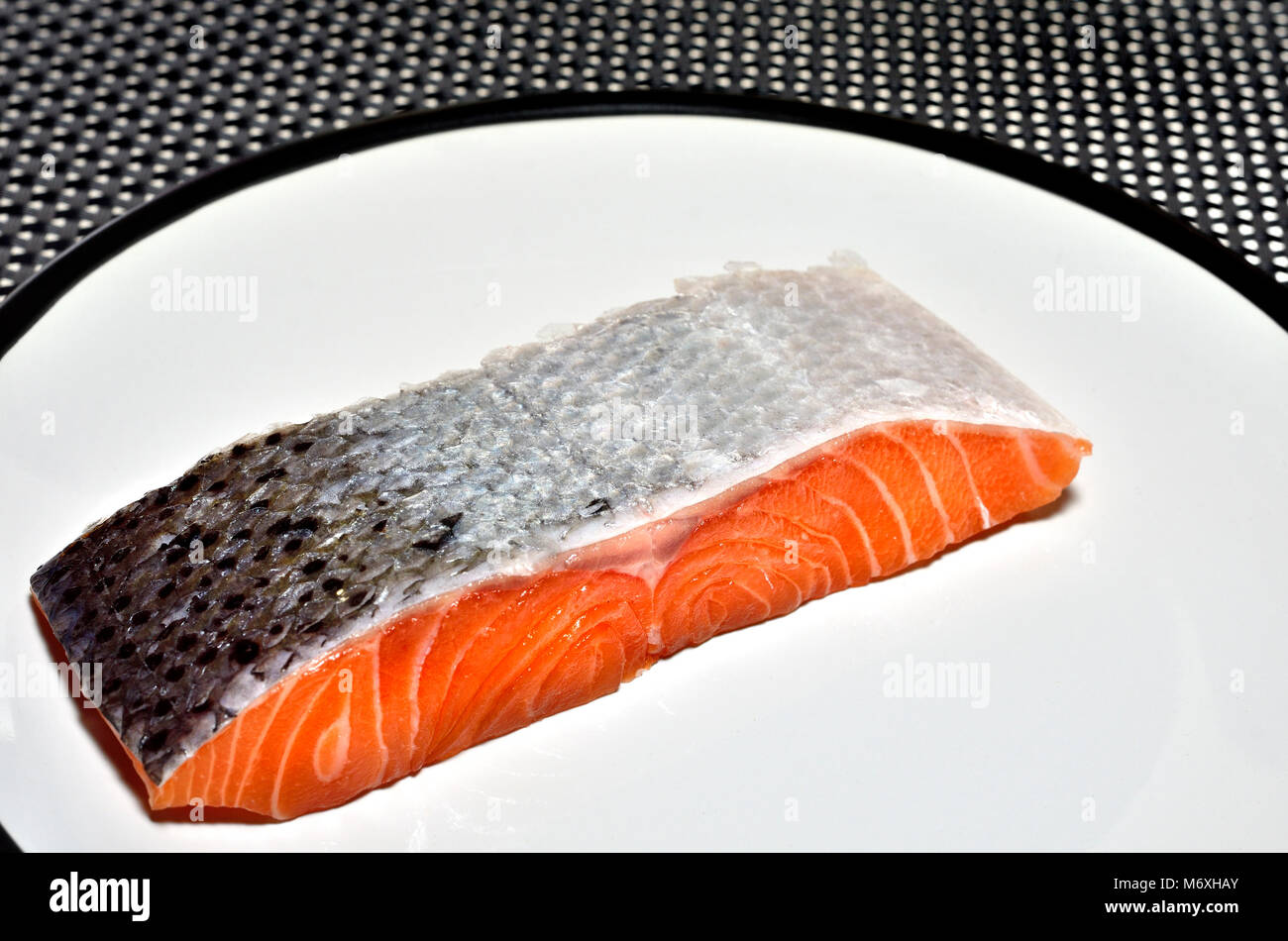 Raw Salmon steak / fillet on a white plate - Stock Image