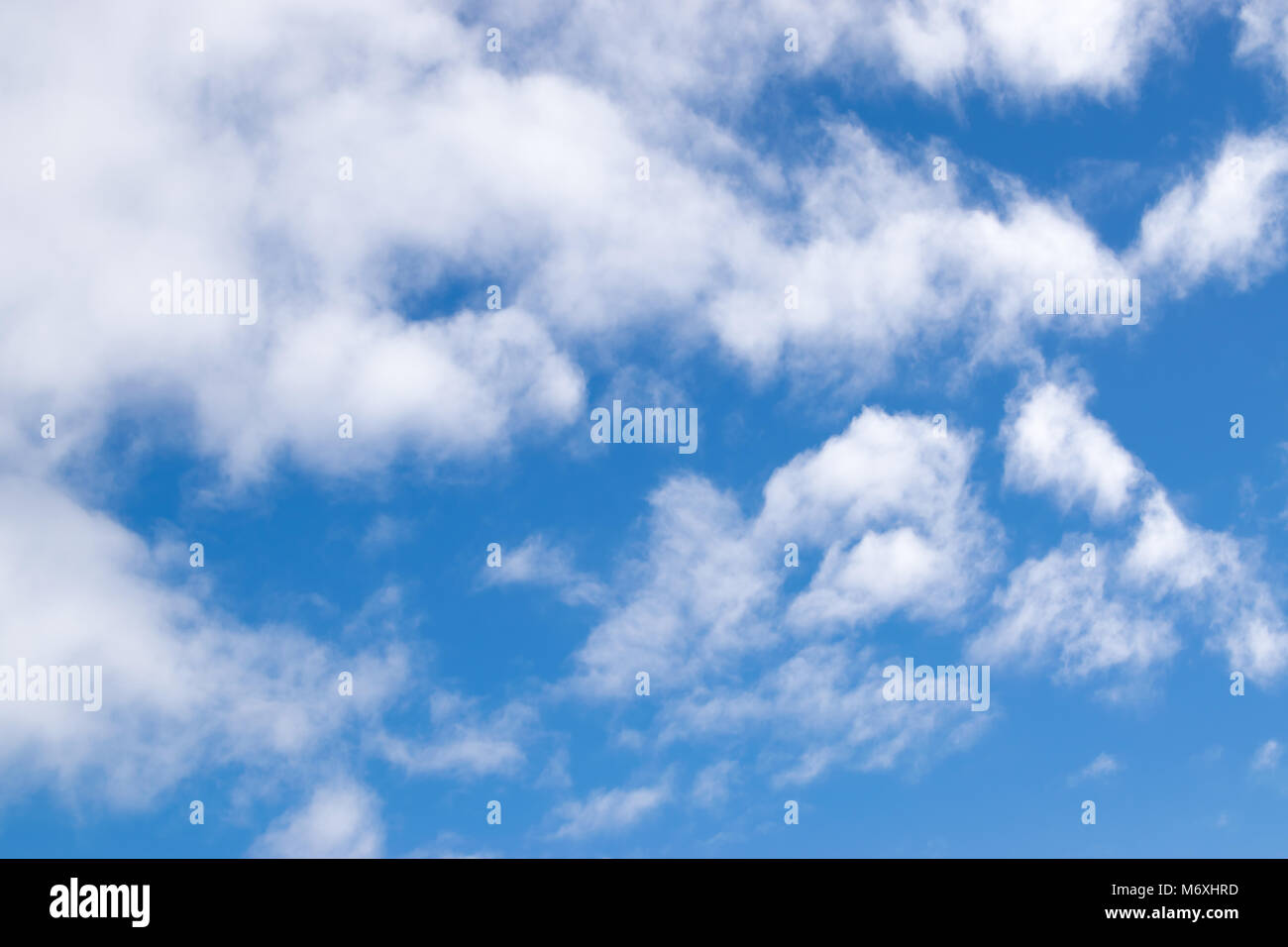 Fluffy clouds against a blue sky - Stock Image