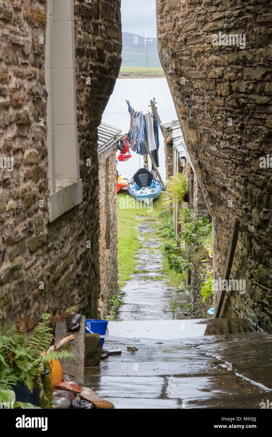 very narrow passageway between houses in Stromness, Orkney, Scotland, UK leading to gardens and the water front - Stock Image