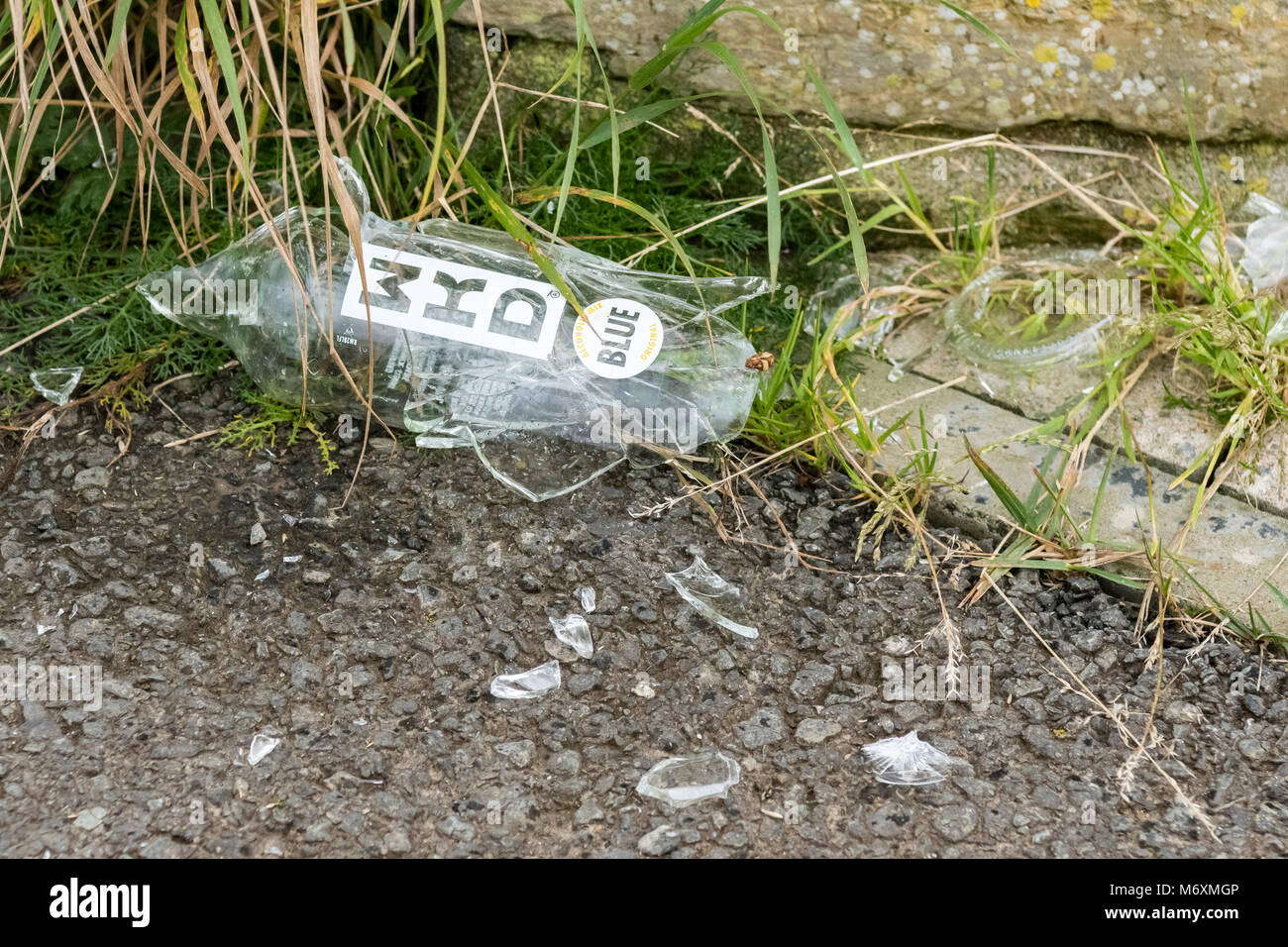 Broken smashed WKD alcohol glass bottle on footpath in Scotland, UK - Stock Image