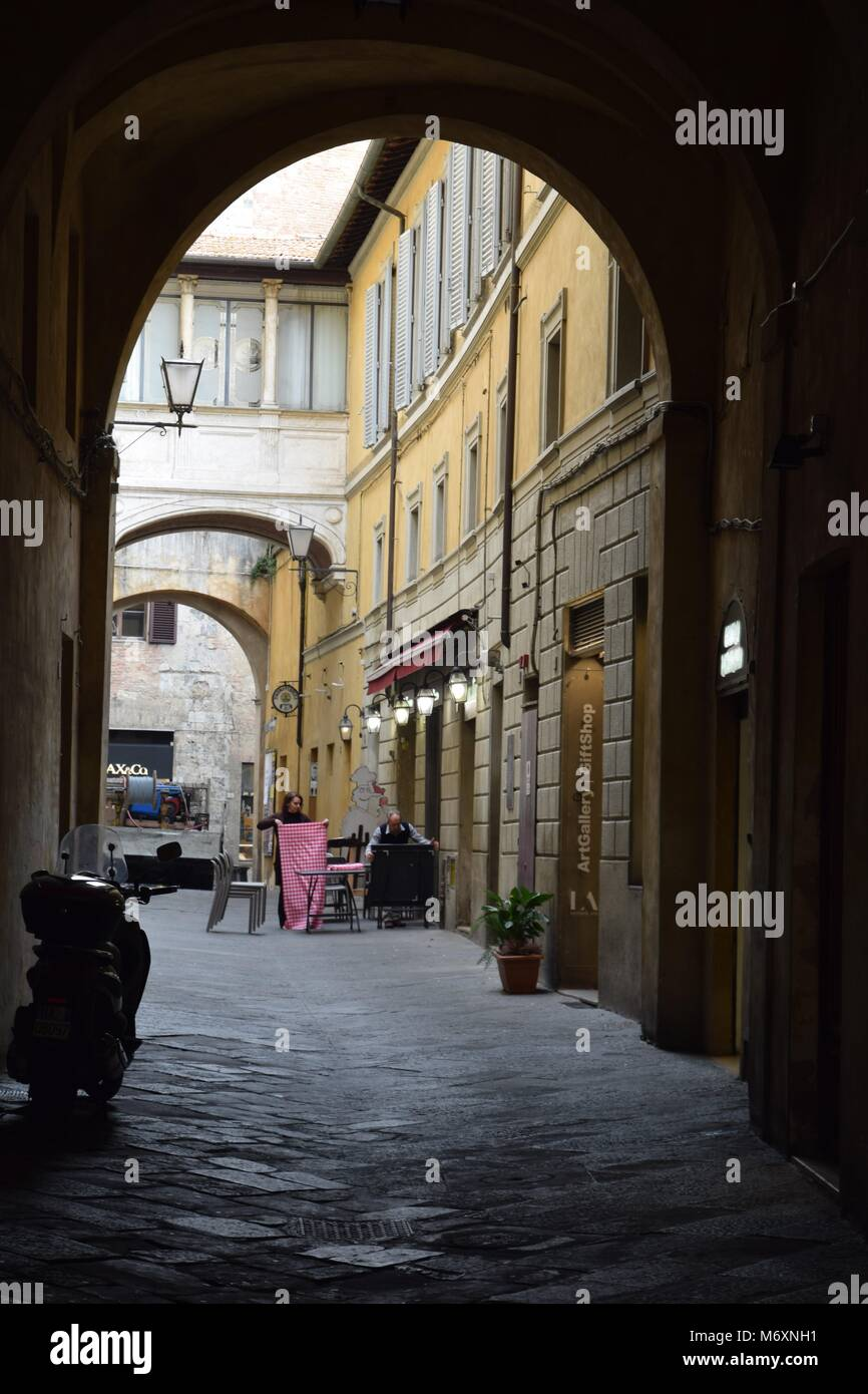 Italian scene: A couple fold tablecloths and tidy away tables after lunch at a restaurant in Siena, Tuscany - Stock Image