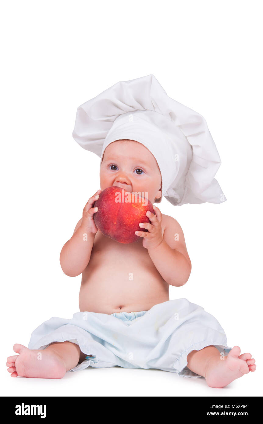 d941fb2f5 A small child is eating a big peach in a chef suit on a white background.