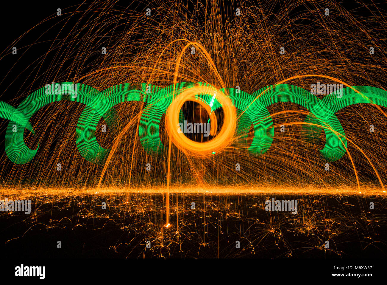 Light painting with steel wool and neon light with effects in orange and green. - Stock Image