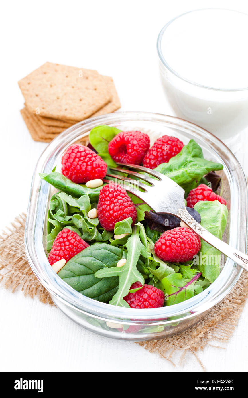 Green  salad with arugula and berries and pine nuts on white table with yogurt - Stock Image