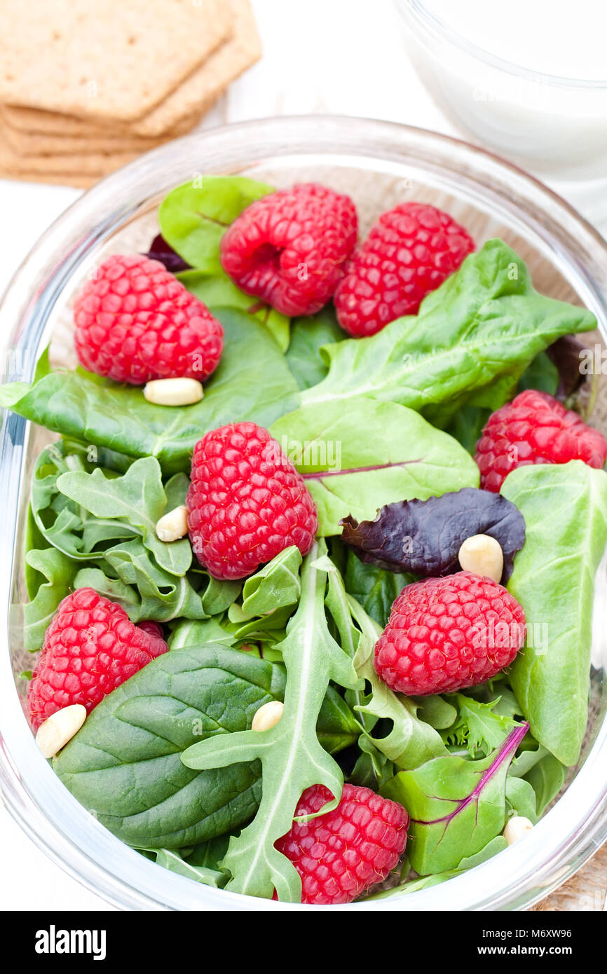 Green  salad with arugula and berries and pine nuts on white - Stock Image