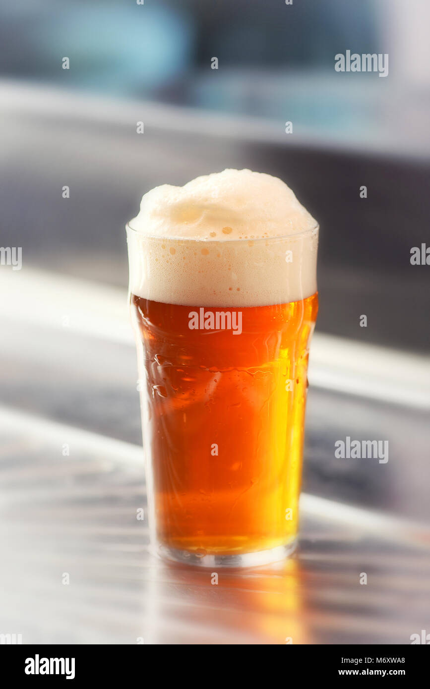 Freshly served pint of frothy draft beer with a good head in a glass on a metal bar counter in a close up side view - Stock Image