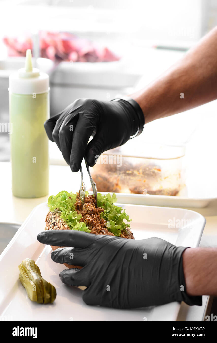 Chef preparing a pulled pork sandwich on a healthy wholegrain roll spooning the tender shredded meat onto fresh - Stock Image