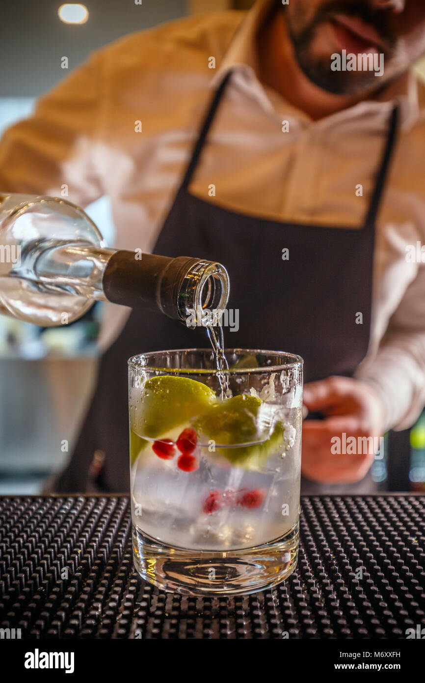 Bartender pouring vodka, Barman at work, preparing cocktails - Stock Image