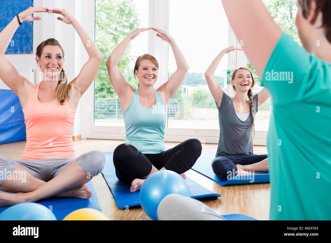 Moms in postnatal regression course doing yoga - Stock Image