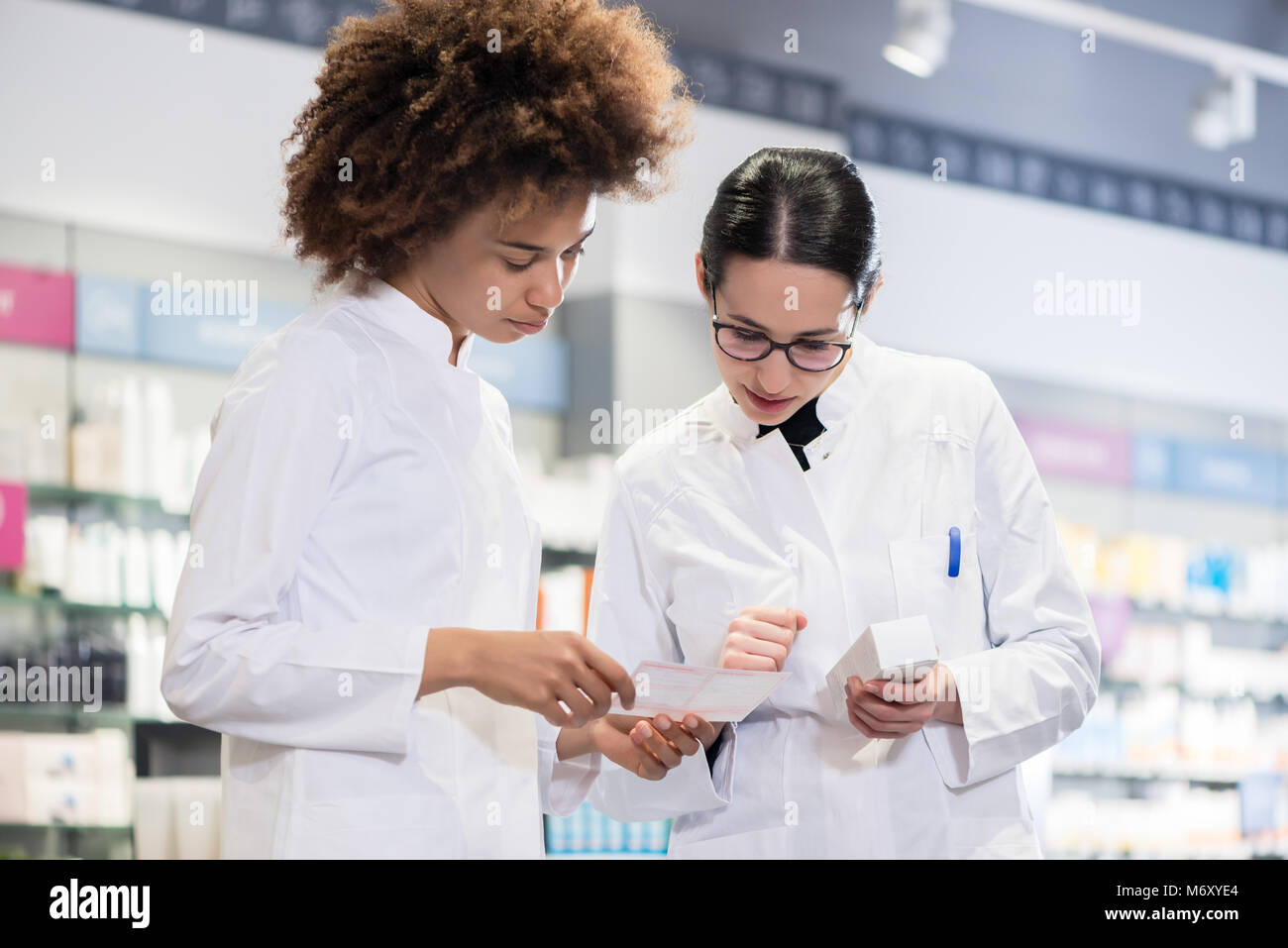 Two pharmacists comparing medicines regarding indications and side effects - Stock Image