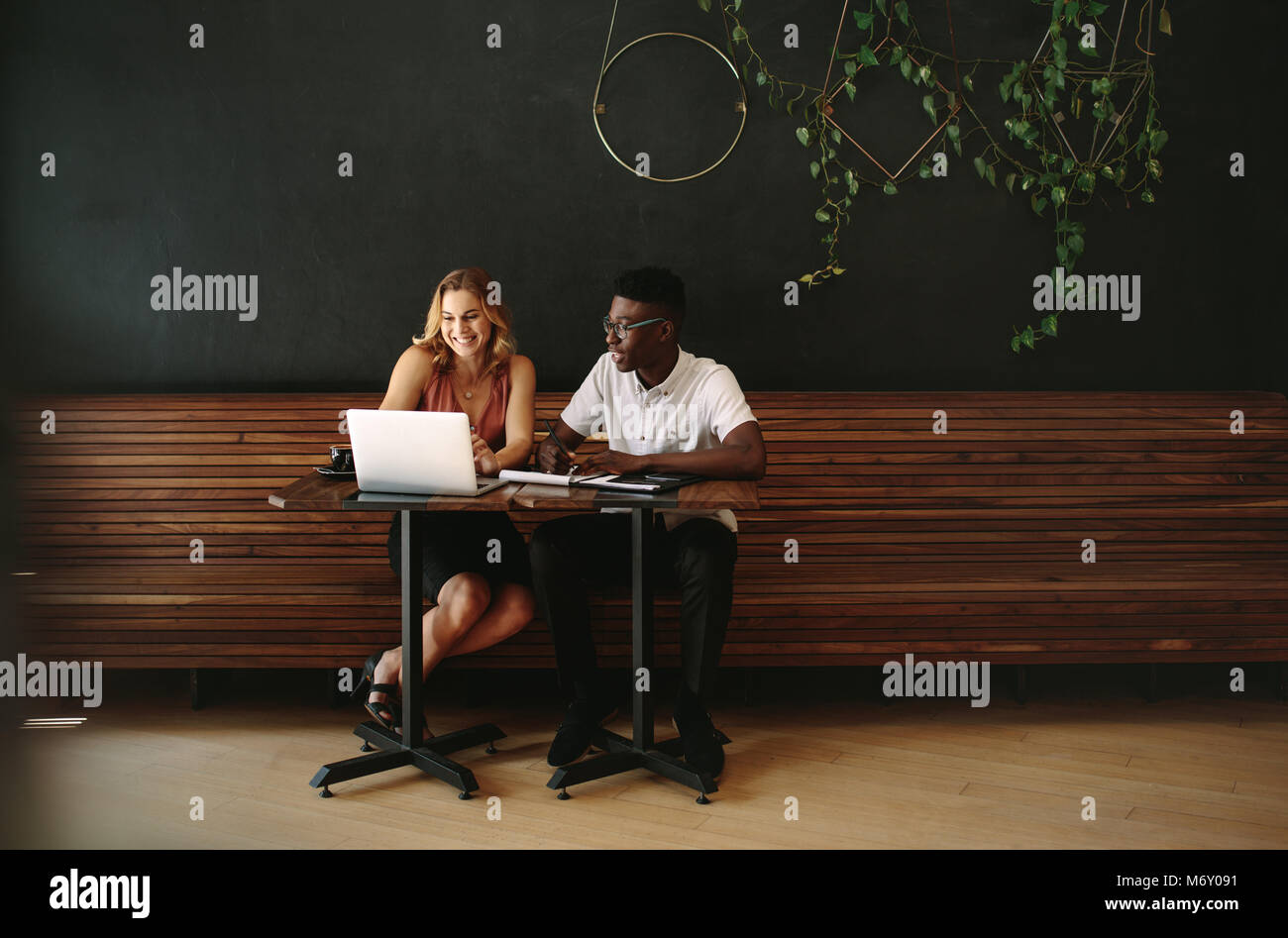 Business partners at a coffee shop working on a laptop computer. Friends sitting at a coffee table with laptop and - Stock Image