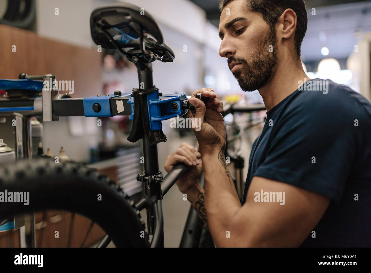 Worker repairing a bicycle at workshop. Man fixing a bicycle to a holding stand in a repair shop. - Stock Image