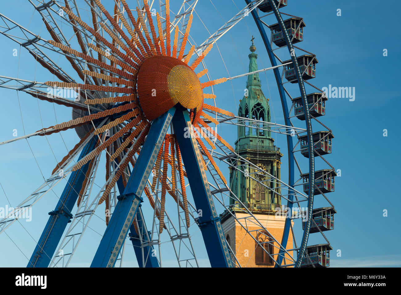 A ferris wheel at Neptunbrunnen with Marienkirche behind, Mitte, Berlin, Germany - Stock Image