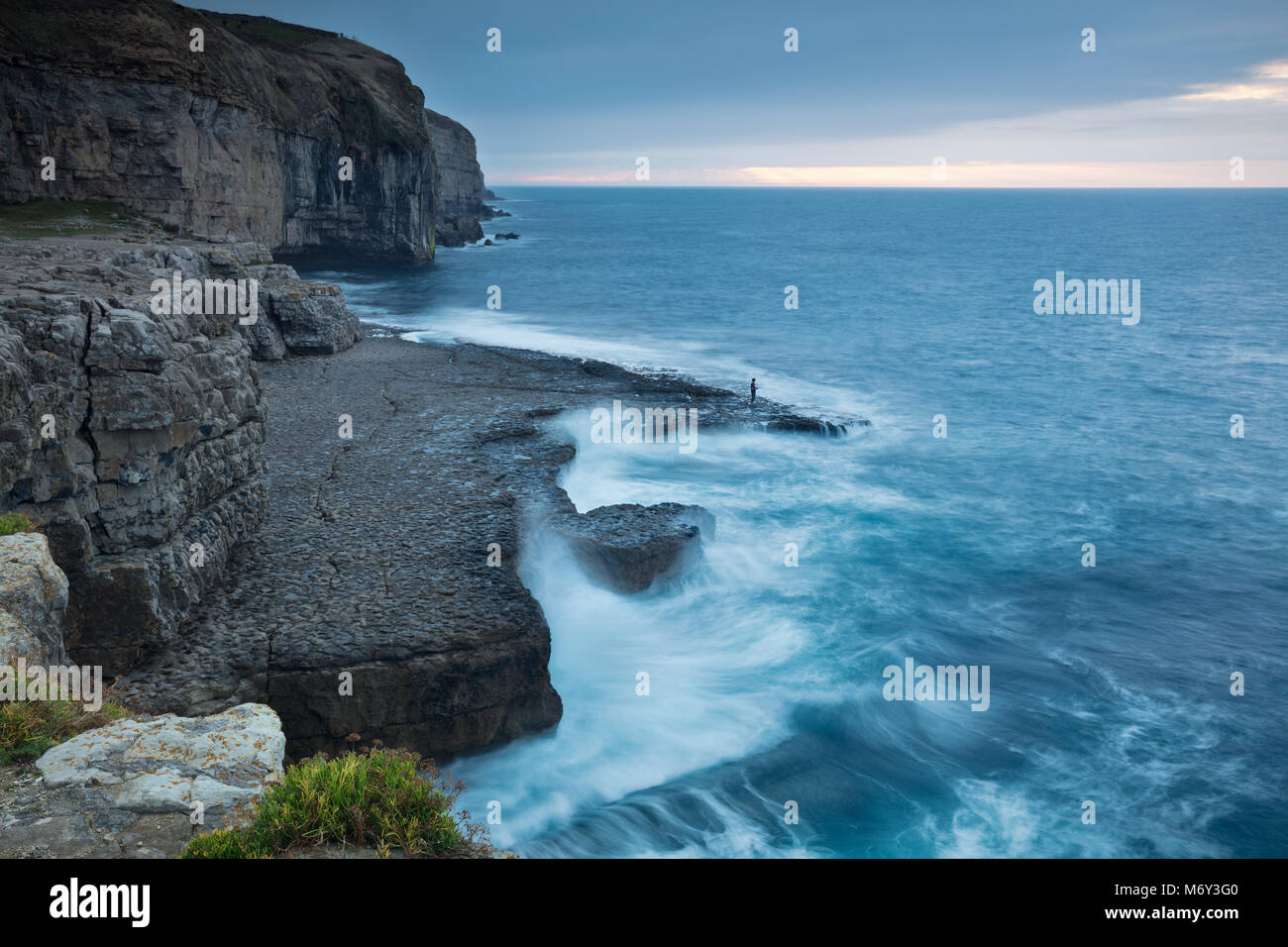 A solitary angler on Dancing Ledge at dawn, Jurassic Coast, Dorset, England, UK - Stock Image