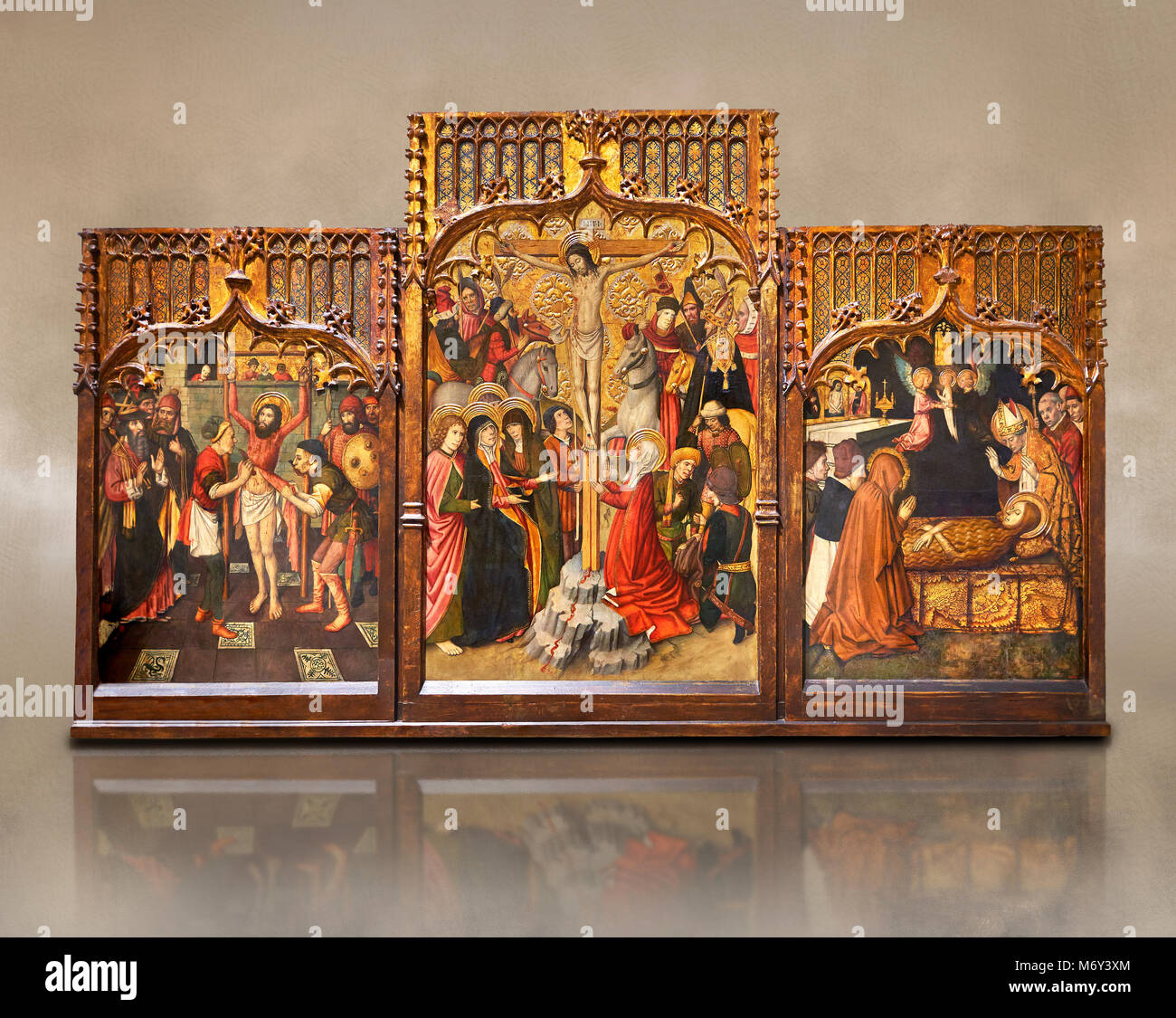 Gothic Catalan altarpiece of, left to right, the martydom of St Bartholomew, Calvaty and the deat of St Mary Magdelene, Stock Photo