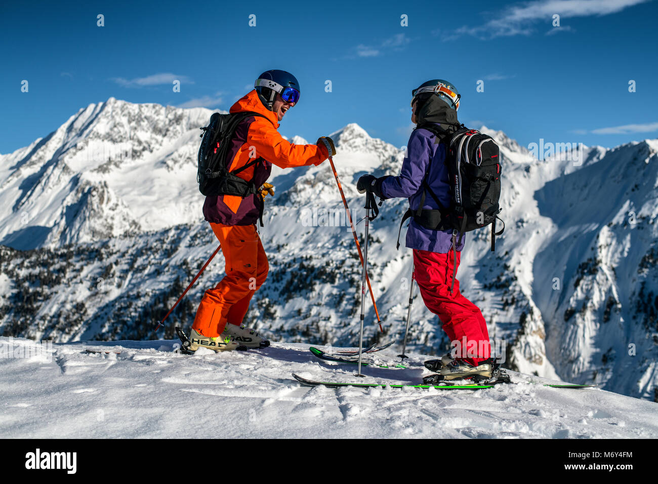 A male ski instructor teaches a woman in the French Alpine resort of Courchevel. - Stock Image