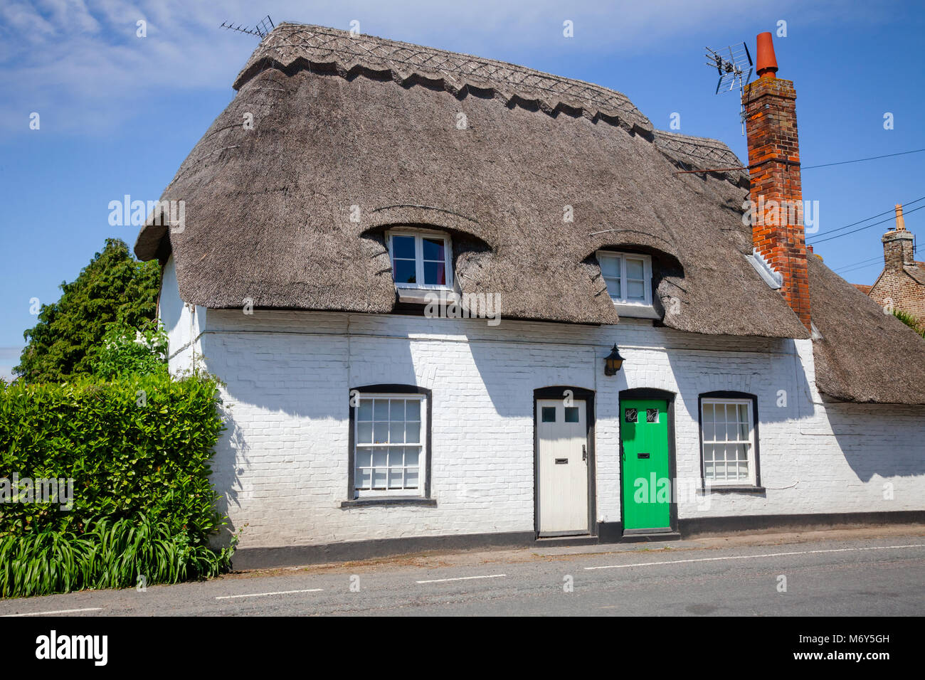 A typical traditional English country thatched house or cottage with white walls in rural Southern England UK - Stock Image