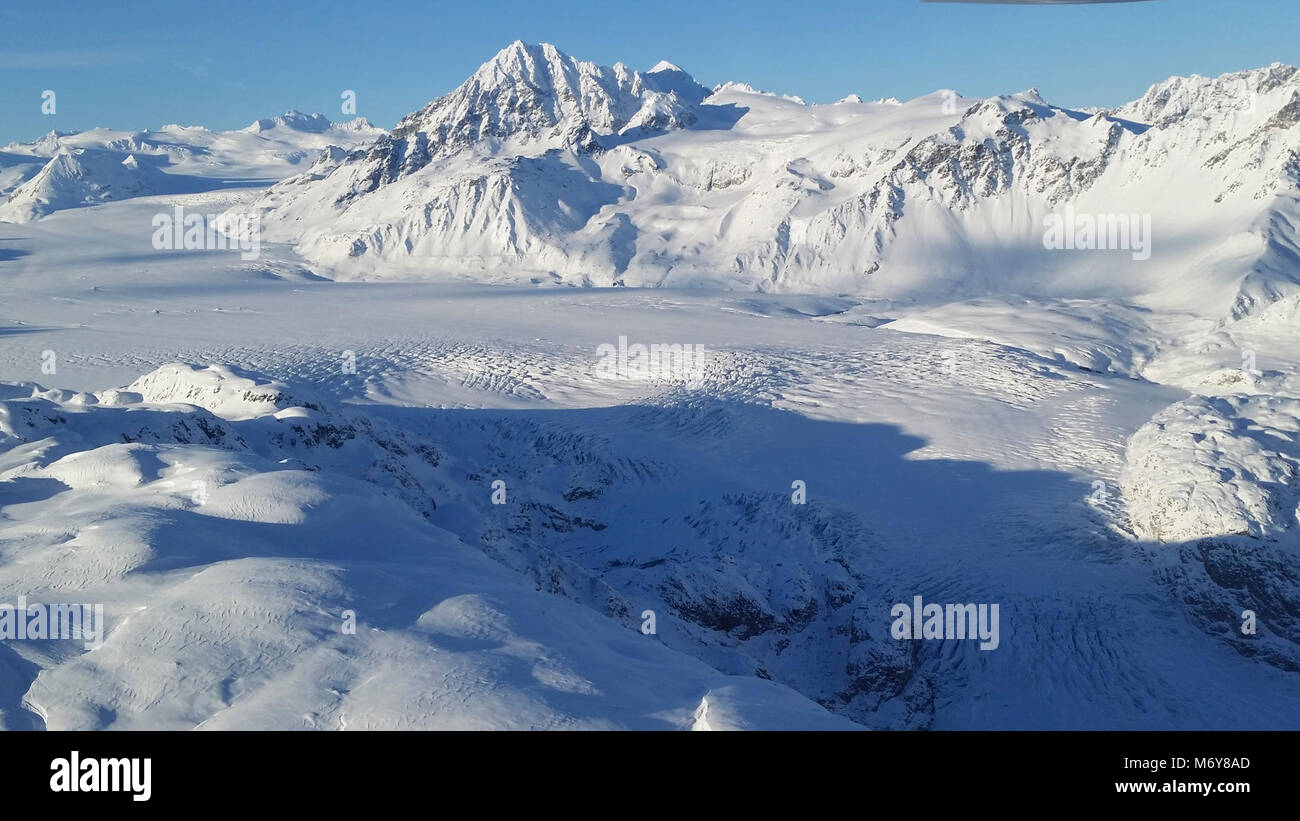 Double Glacier   . A glacier between snow covered mountains in the Chigmit range - Stock Image