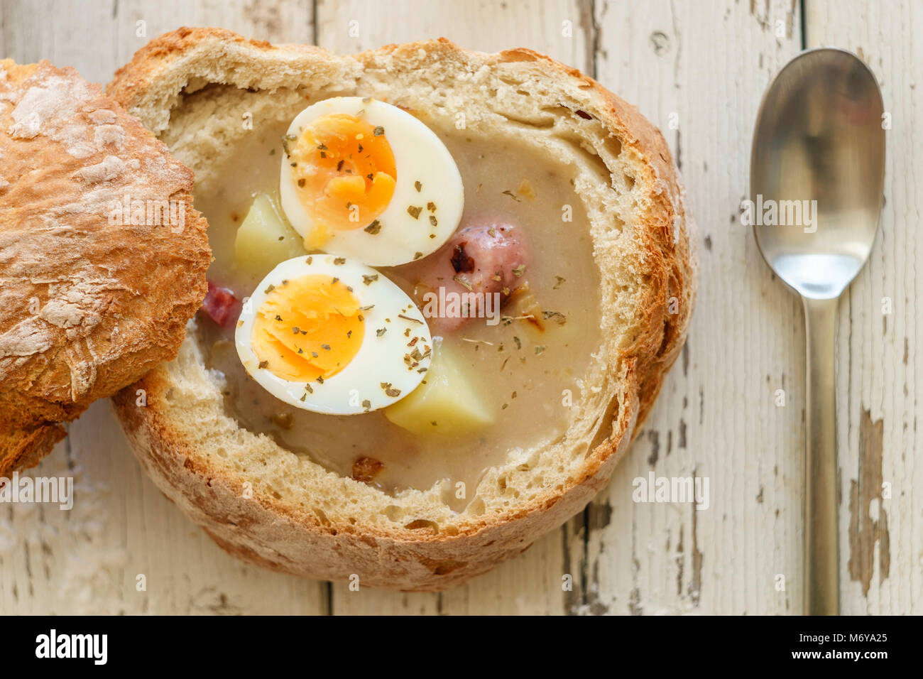 Traditional polish soup called Zurek with eggs and  sausage on wooden background - Stock Image
