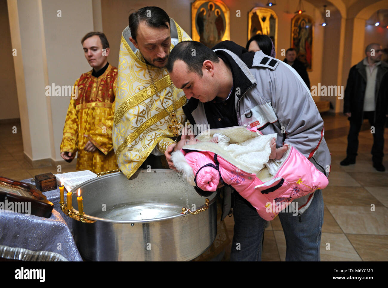 Christening for baby in a rural church. Priest standing in front of a man with a baby on hands and baptizing a child. - Stock Image
