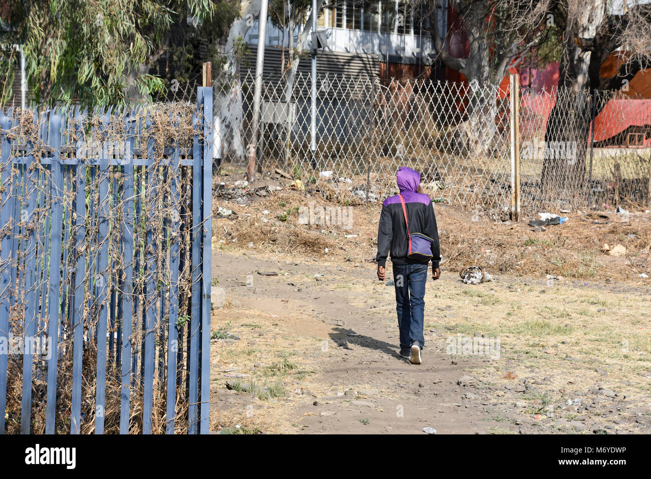 A male walking near a gate with barbed razor wire in Pretoria South Africa used as steel fencing constructed with - Stock Image
