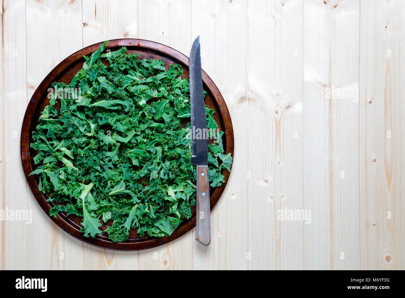 Fresh chopped prepared kale on old metal platter with knife - Stock Image