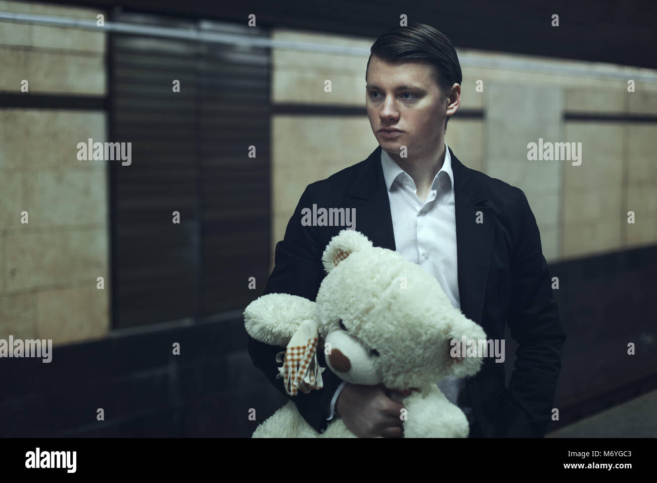Sad young guy holds a stuffed toy and waits for a lover. - Stock Image