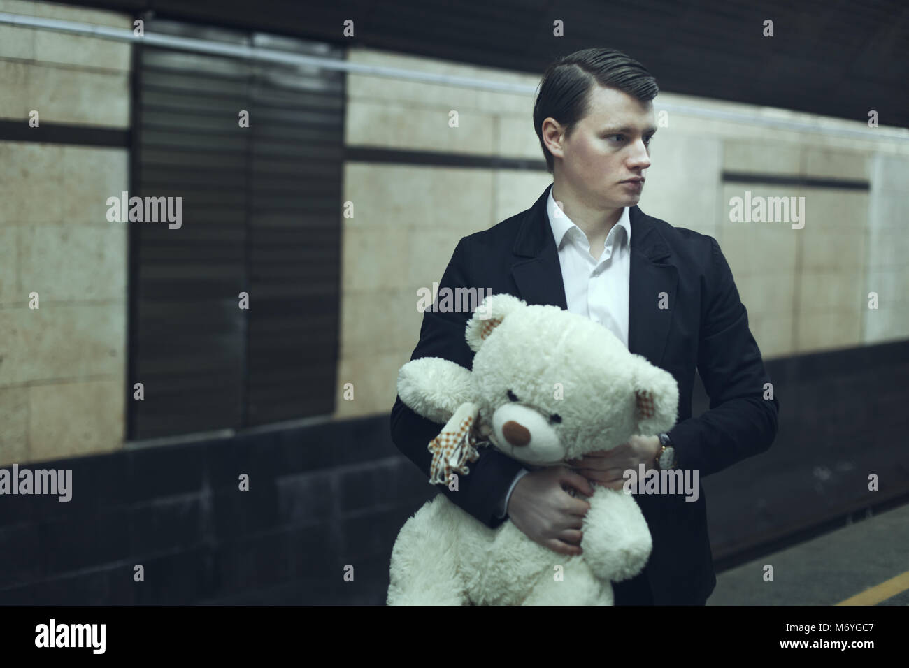 Young man with a teddy bear, he worries before the meeting. - Stock Image
