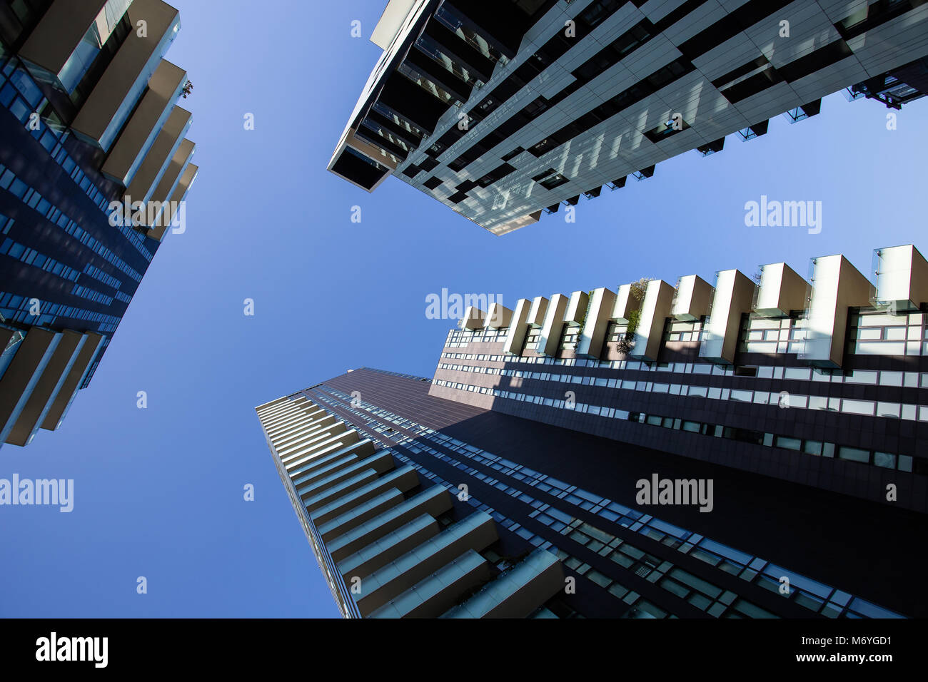 One point perspective looking straight up towards clear blue sky from ground level of tall skyscraper buildings Stock Photo
