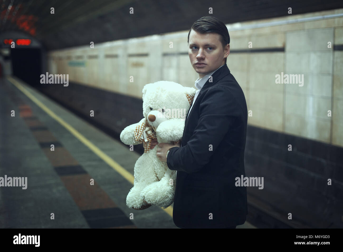 Sad young man with a teddy bear in his hands is standing at a subway station. - Stock Image