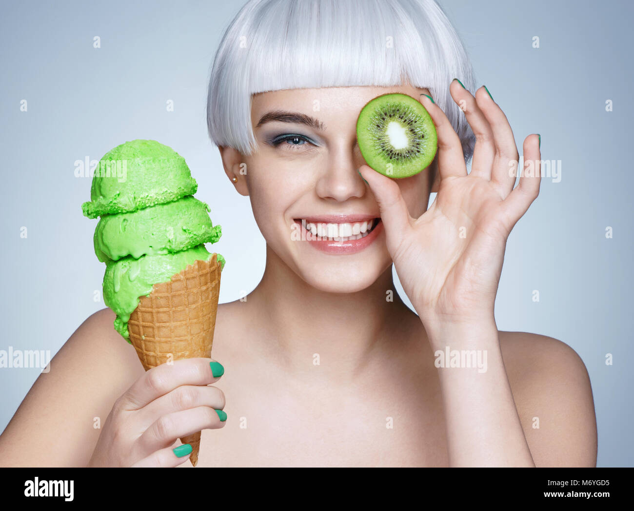 567e7beec03d Funny young girl holding waffle cone with ice cream and kiwi fruit. Photo  of smiling