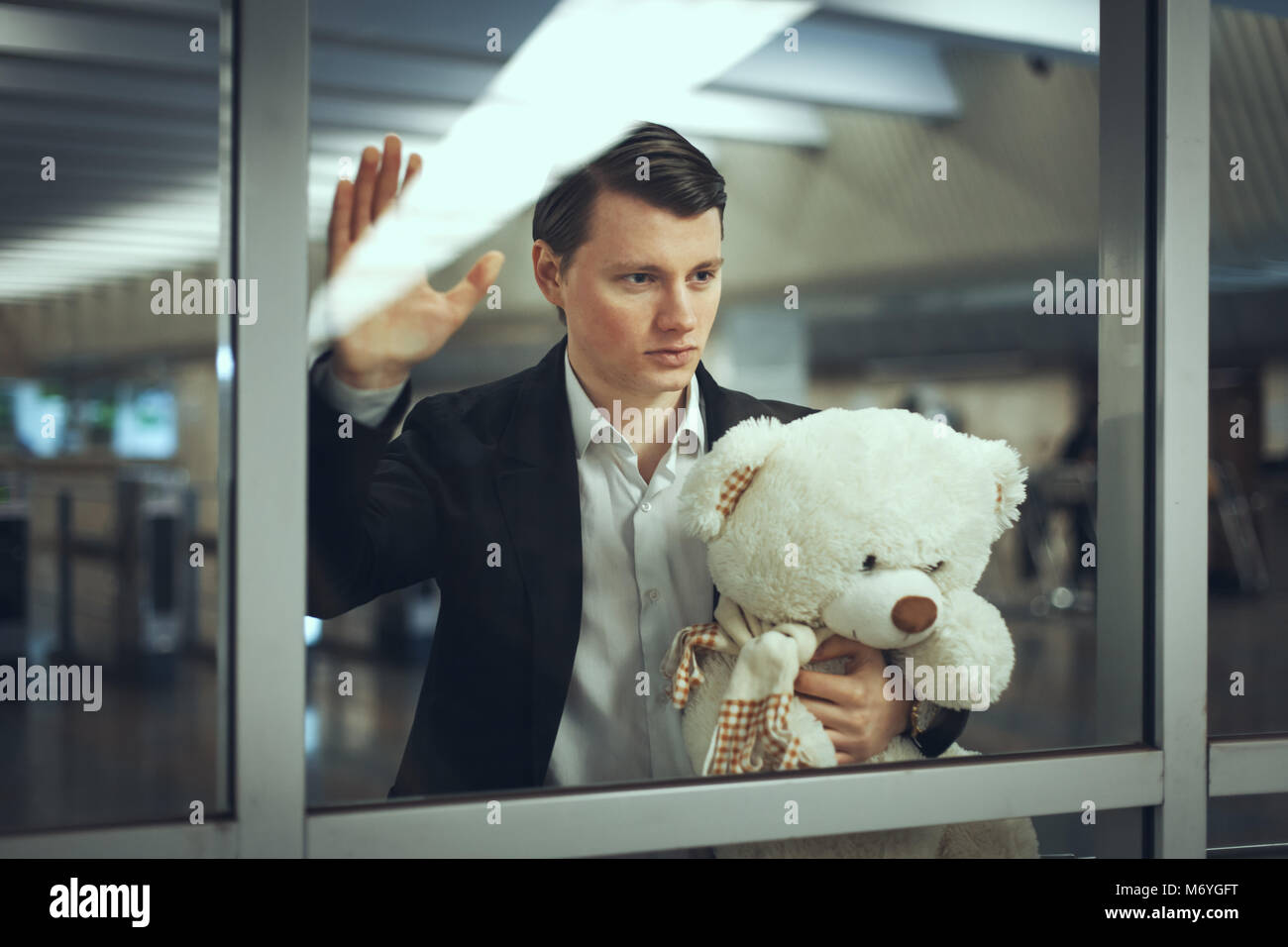 Sad man with a toy bear waiting for a meeting. He looks out the window Stock Photo