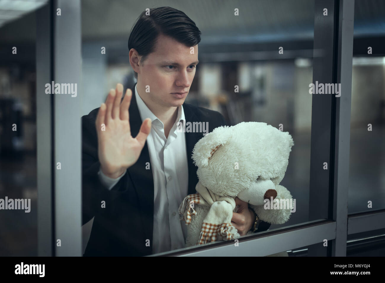 Young man looks out the window and waits for a meeting. He has a teddy bear in his hands Stock Photo