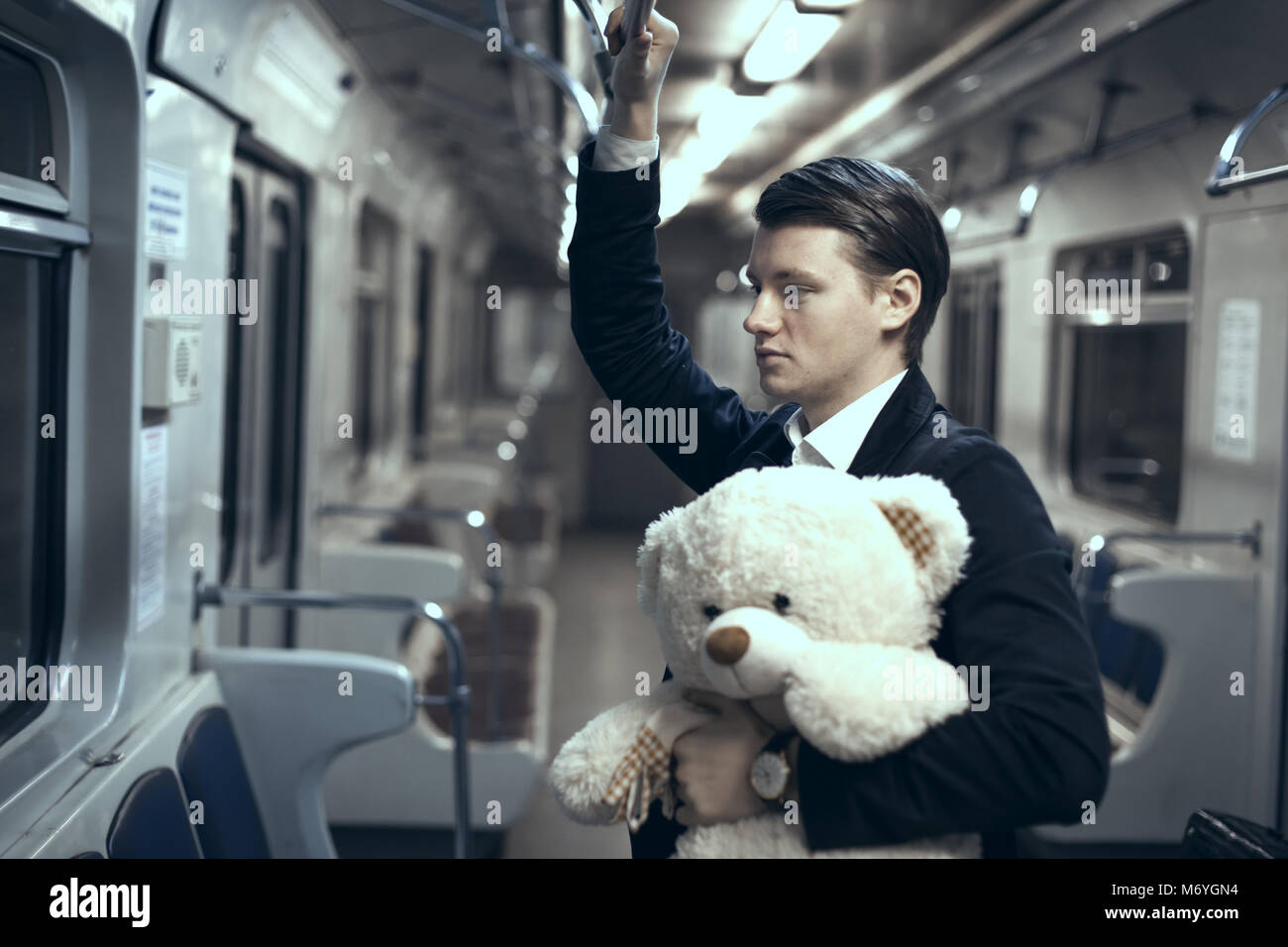 Young man is riding in an empty subway car. In his hands is a teddy bear - Stock Image