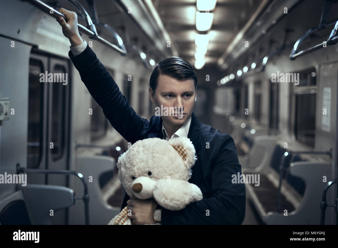 Guy with a teddy bear in the subway. In an empty car he is lonely, it makes him sad. - Stock Image